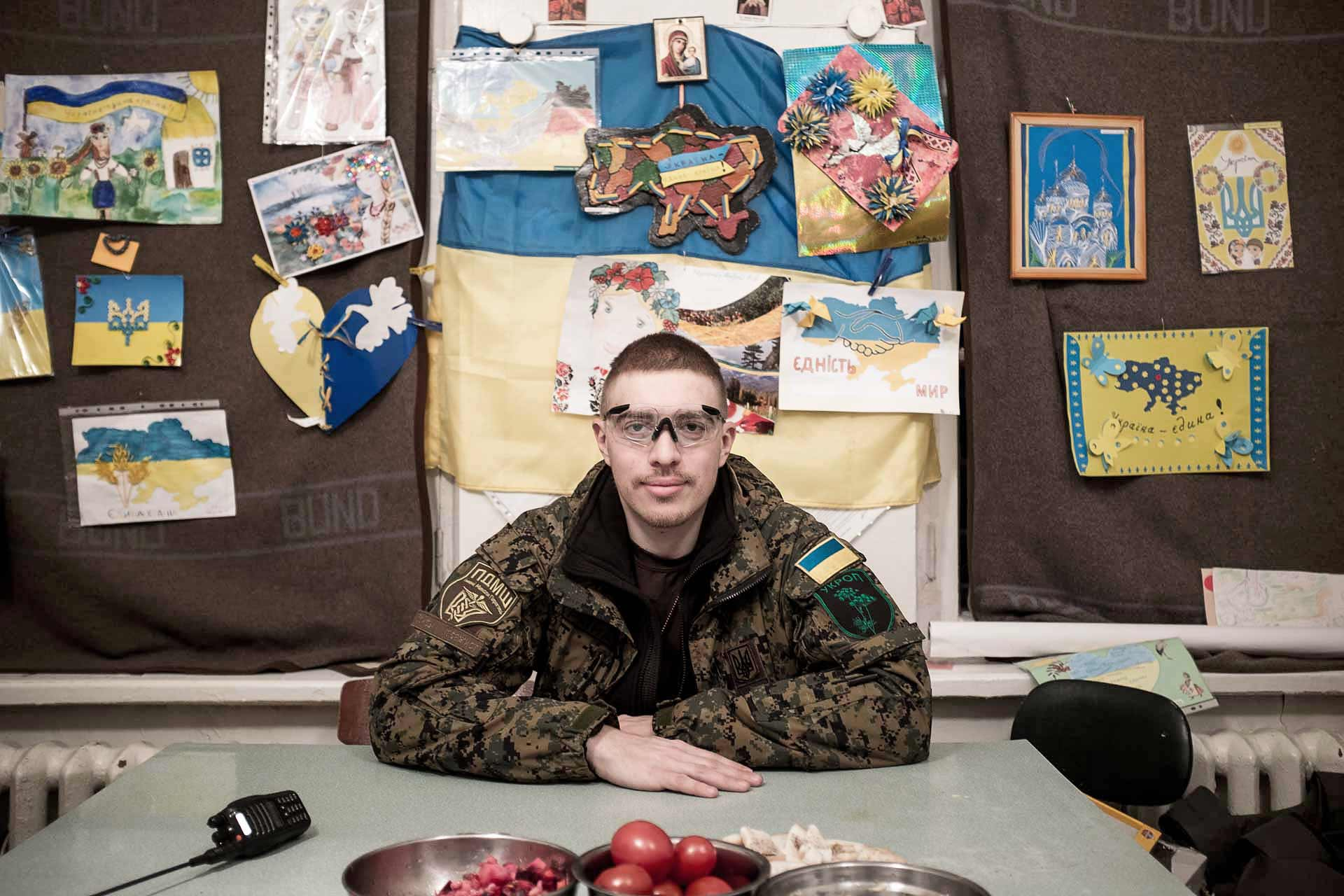 Evgen, volunteer, 30, from Mykolaiv, is a massager in civil life, joined the medical unit of mobile hospital in October 2014. Behind him, the drawings that were performed by Ukrainian children to support the soldiers. Thousands of these drawings from all part of Ukraine are sent to the soldiers on all the front lines to cheer them up. Bakhmout (UKRAINE)
