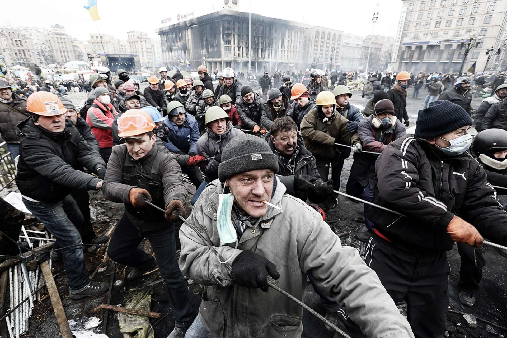 Maidan square, an opposition group trying to overthrow the carcass of a bus to make a barricade - Kyiv, UKRAINE, february 2014